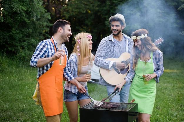 Gruppo di amici di persone in piedi intorno alla griglia, chiacchierando, bevendo e mangiando.