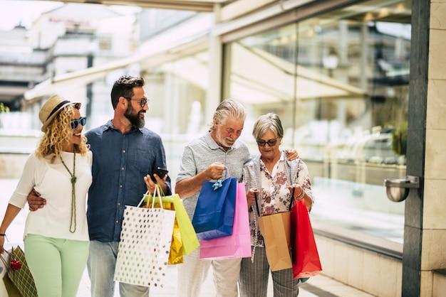 Un gruppo di persone va a fare shopping insieme con un sacco di borse sulle braccia e si tiene con le mani al centro commerciale o al grande negozio - la famiglia si diverte a comprare vestiti insieme per fare regali per natale