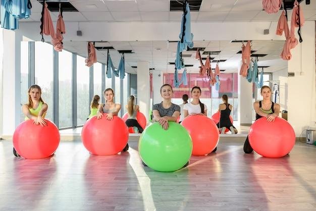 Gruppo di persone in palestra che sorridono con una palla da pilates