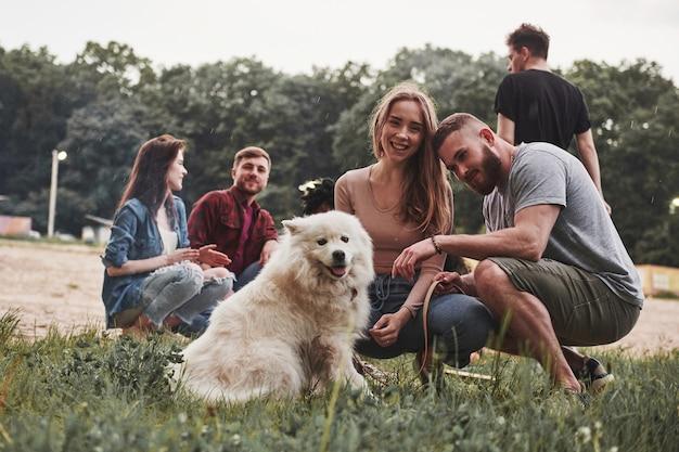 Un gruppo di persone fa un picnic sulla spiaggia. gli amici si divertono durante il fine settimana.
