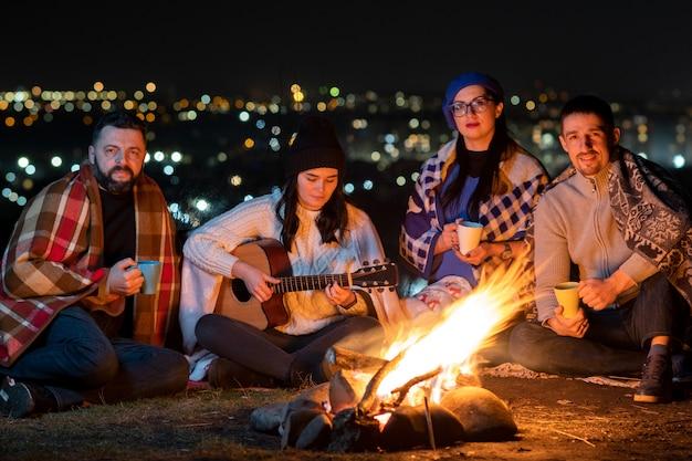 Gruppo di persone che si divertono seduti vicino al falò all'aperto di notte suonando la chitarra, cantando canzoni e parlando felicemente insieme.