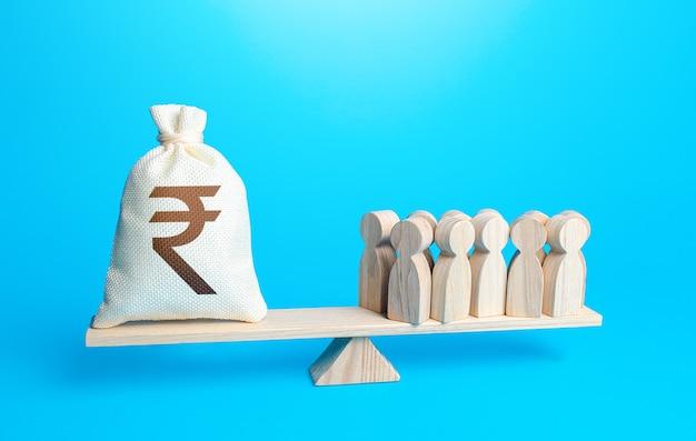 Gruppo di persone e borsa dei soldi della rupia indiana sulle bilance manutenzione del personale