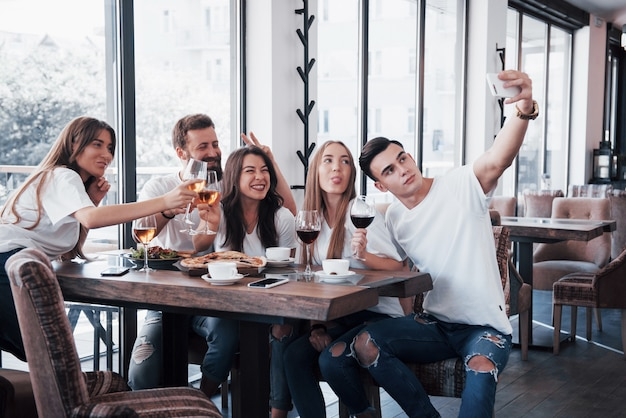 Un gruppo di persone fa una foto selfie in un caffè. i migliori amici si sono riuniti a tavola per mangiare la pizza e cantare vari drink