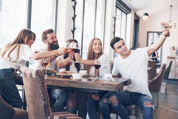 Un gruppo di persone scatta una foto selfie in un bar. i migliori amici si sono riuniti a tavola mangiando pizza e cantando vari drink.