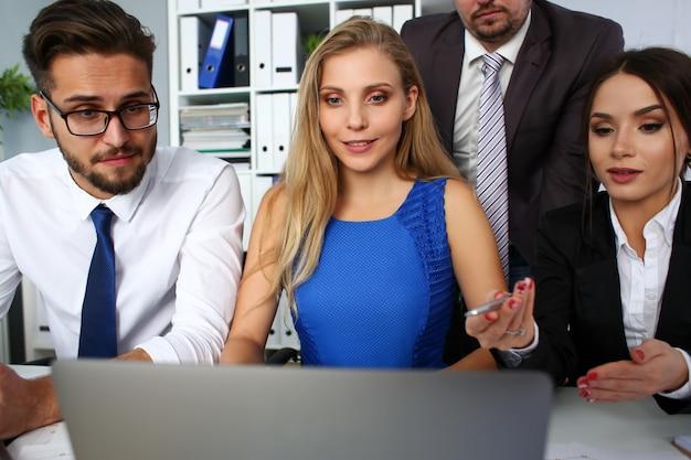 Il gruppo di persone in ufficio usa il ritratto del pc del computer portatile