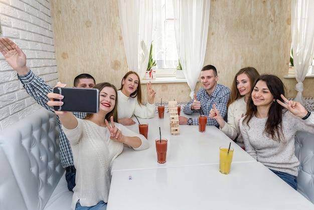 Gruppo di persone che giocano a torre al bar e si fanno selfie