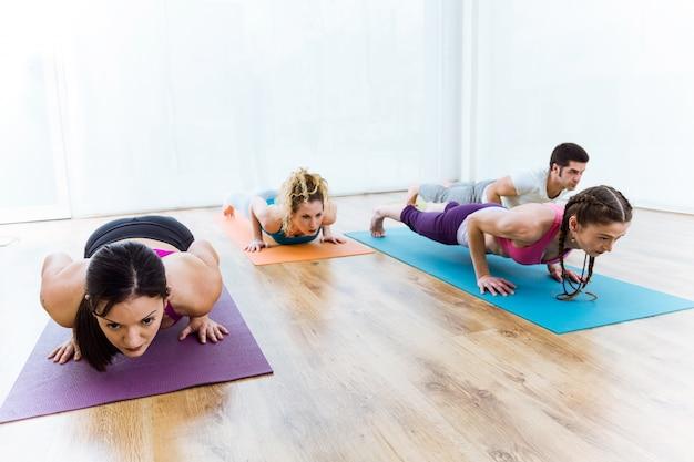 Gruppo di persone che praticano yoga a casa. chaturanga dandasana posa.