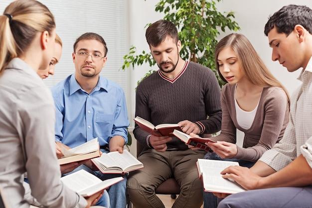 Gruppo di persone che leggono insieme il libro della bibbia