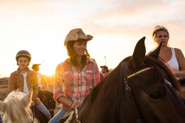 Gruppo di persone a cavallo insieme divertendosi e imparando a cavalcare - camminando su un cavallo