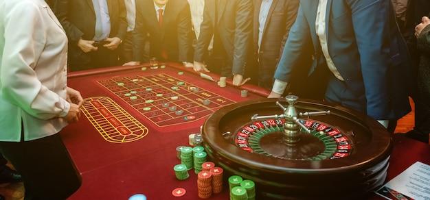 Gruppo di persone dietro il tavolo da gioco della roulette nel casinò di lusso
