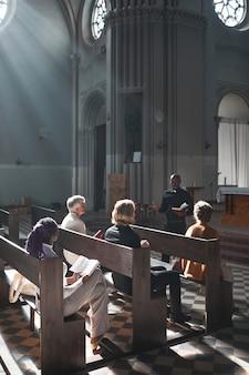 Gruppo di persone sedute sulla panchina che ascoltano il discorso del sacerdote durante la messa