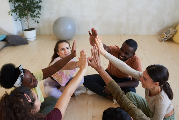 Gruppo di persone sedute sul pavimento e dando il cinque durante la lezione di terapia