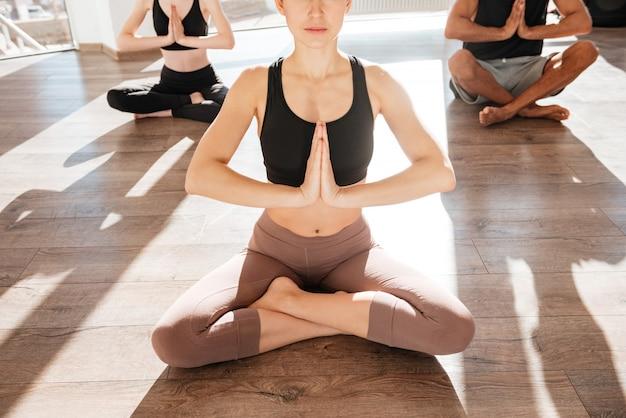 Gruppo di persone che si siedono nella posa del loto e che praticano yoga