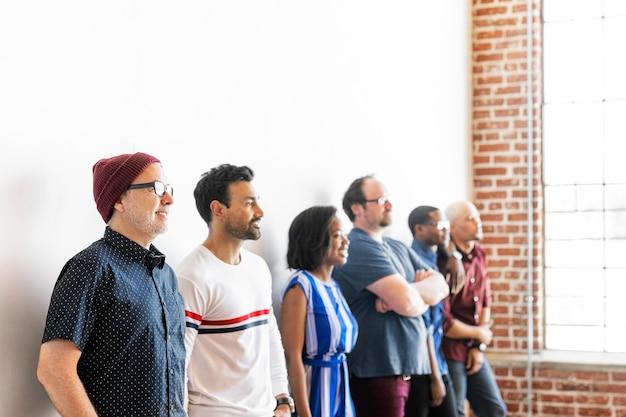 Gruppo di persone in piedi vicino a un muro bianco