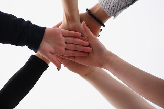 Gruppo di persone in giacca e cravatta incrociate le mani in pila per la vittoria
