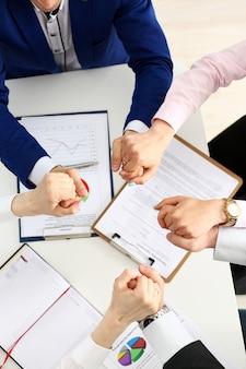 Gruppo di persone in giacca e cravatta incrociate le mani nel mucchio