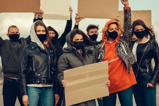 Un gruppo di persone con maschera e poster per protestare la protesta della popolazione contro il coronavirus e contro l'introduzione della quarantena