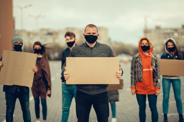 Un gruppo di persone con maschera e poster per protestare la protesta della popolazione contro il coronavirus