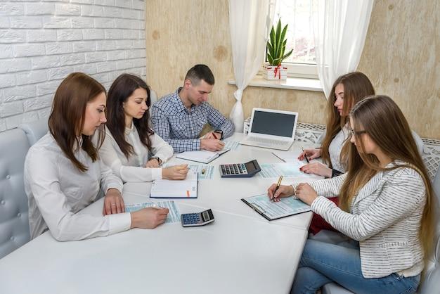 Gruppo di persone che lavorano con modulo 1040 in ufficio