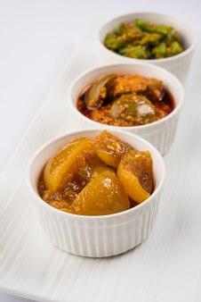 Fotografia di gruppo di sottaceti indiani come sottaceti al mango, sottaceti al limone e sottaceti al peperoncino verde, sarved in una ciotola di ceramica nera, messa a fuoco selettiva
