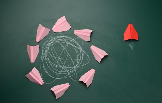 Un gruppo di aerei rosa vola in cerchio con una traiettoria intricata e uno vola in un percorso rettilineo. il concetto di pensare fuori dagli schemi, unicità. soluzioni aziendali veloci