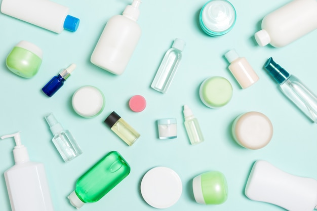 Il gruppo di bottiglia di plastica del bodycare la composizione piana nella disposizione con i prodotti cosmetici sullo spazio vuoto del fondo blu per voi progetta. set di contenitori cosmetici bianchi, vista dall'alto con spazio di copia