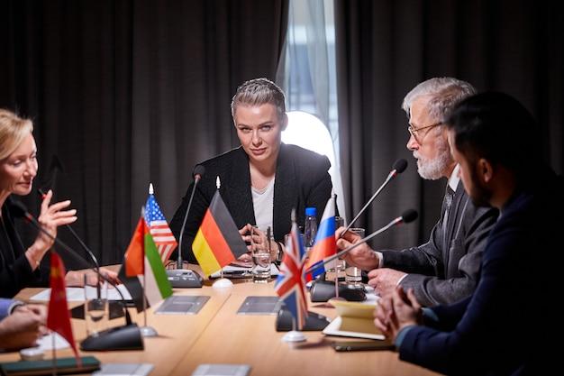 Gruppo di leader politici seduti con i microfoni in conferenza stampa, parlare, tenere una riunione senza legami per discutere idee e questioni all'ordine del giorno. nella moderna sala riunioni