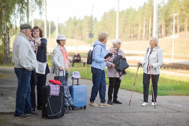 Un gruppo di viaggiatori anziani anziani positivi che aspettano il treno prima di partire per un viaggio