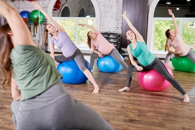 Gruppo di donne incinte che allungano nella classe di forma fisica