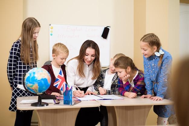 Gruppo di scolari primari e insegnanti che lavorano alla scrivania in aula.