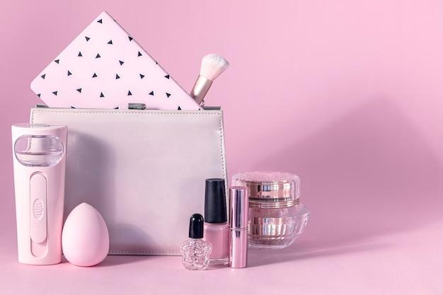 Gruppo di cosmetici professionali per il trucco su sfondo rosa con ombra e spazio di copia