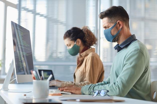 Gruppo di programmatori in maschera seduti al tavolo e lavorando con i codici sui computer durante la pandemia
