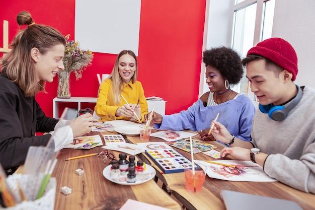 Progetto di gruppo. compagnia di quattro studenti d'arte che si sentono coinvolti nel lavoro su un progetto di gruppo