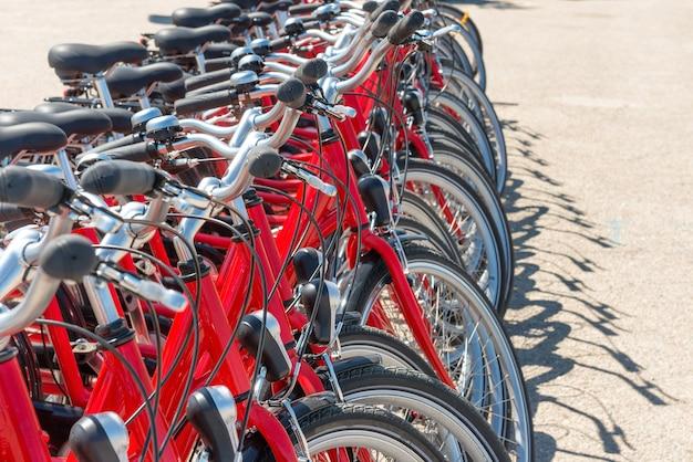 Gruppo di biciclette rosse della città che parcheggiano sulla strada