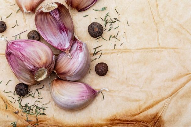 Gruppo di spicchi d'aglio rosso, palline di pepe nero e altre spezie. su uno splendido sfondo rustico color vaniglia. spazio per inserire il testo (copia testo)