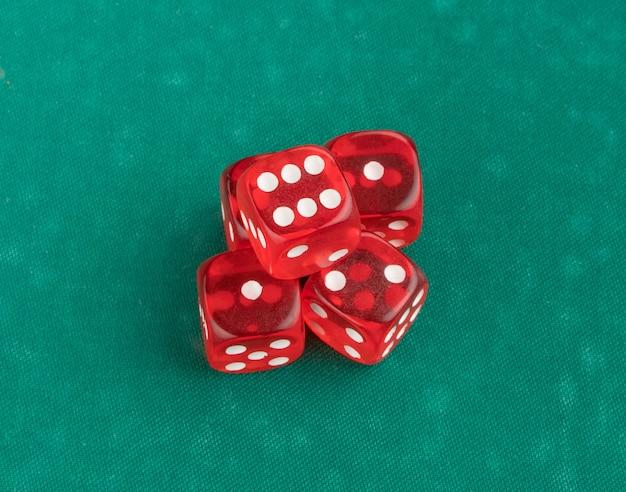 Gruppo di dadi rossi da gioco su sfondo verde, isolato. vista dall'alto