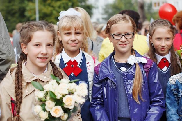 Un gruppo di studentesse con fiocchi, fiori va in vacanza per l'istruzione, sorride e gioisce.