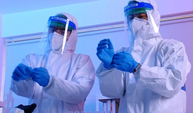 Gruppo di scienziati che indossano dispositivi di protezione individuale (dpi) in laboratorio.