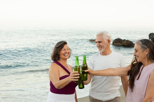 Gruppo di amici anziani che esultano con la birra in spiaggia