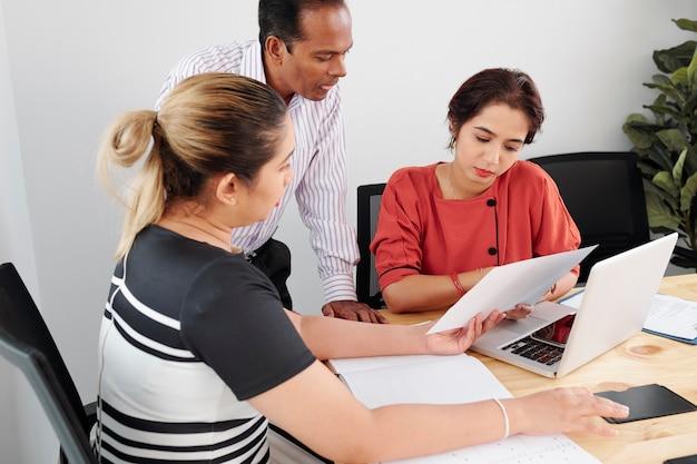 Un gruppo di dirigenti aziendali seri si è riunito al tavolo dell'ufficio per discutere i rapporti con i dati di vendita