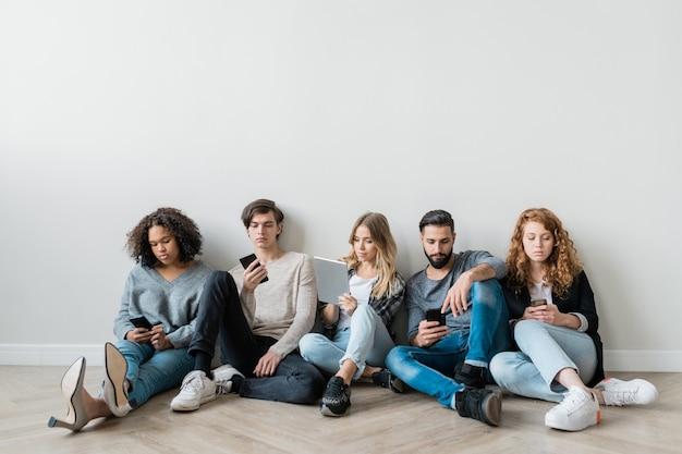 Gruppo di millennial seri con smartphone e touchpad che scorrono i gadget mentre sono seduti sul pavimento vicino al muro