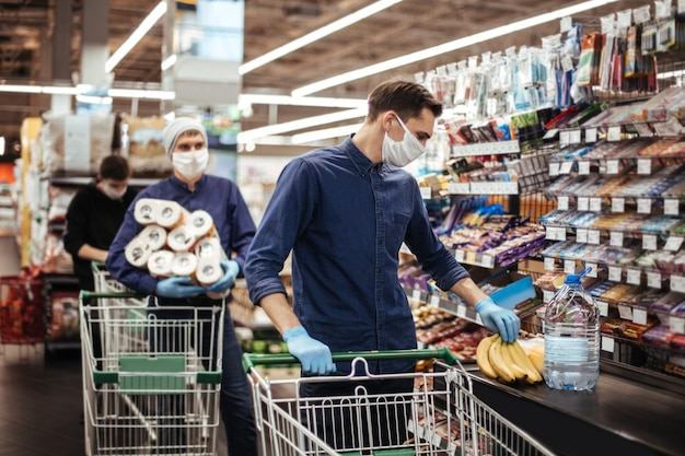 Gruppo di acquirenti in maschere protettive in piedi vicino alla cassa in un supermercato. igiene e assistenza sanitaria
