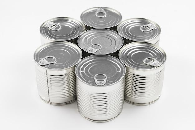 Gruppo di cibo in scatola d'argento su sfondo bianco.