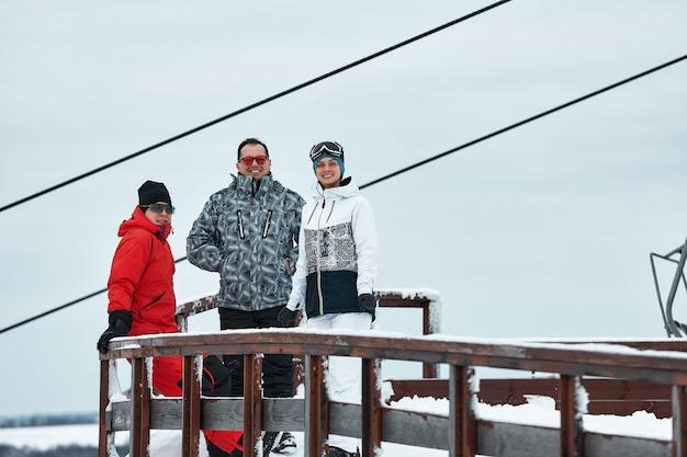 Un gruppo di amici sciatori sulla montagna sta riposando e bevendo caffè da un thermos sulla superficie dello skilift