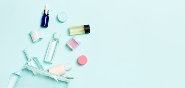 Gruppo di piccole bottiglie per viaggiare su sfondo blu. copia spazio per le tue idee. composizione piatta di prodotti cosmetici.