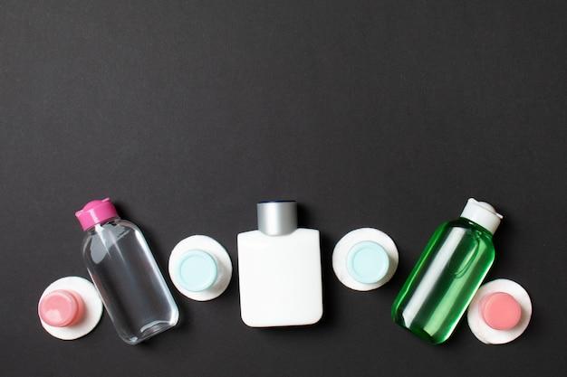 Gruppo di piccole bottiglie per viaggiare su sfondo colorato. copia spazio per le tue idee. composizione piatta di prodotti cosmetici. vista dall'alto di contenitori crema con tamponi di cotone.