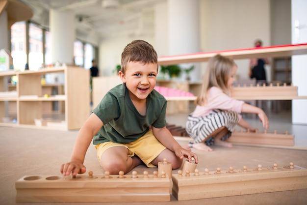 Gruppo di piccoli bambini della scuola materna che giocano al chiuso in classe, apprendimento montessori.