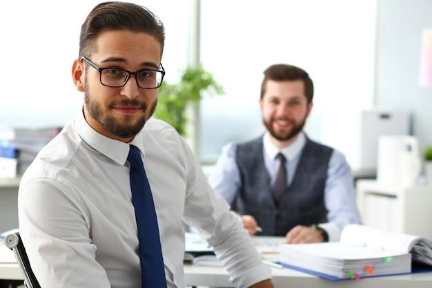 Gruppo di uomini d'affari barbuti sorridenti in giacca e cravatta