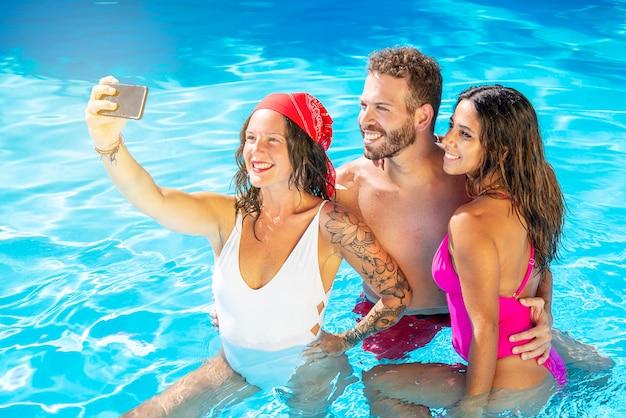 Gruppo di amici sorridenti insieme in piscina prendendo selfie