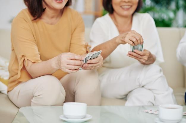Gruppo di amiche anziane sorridenti che giocano a carte a casa e bevono caffè